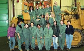 BCIT women in trades; heavy duty, students in uniforms standing in front of a bulldozer [5 of 9 p...