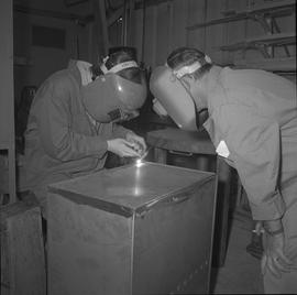 Sheet metal, 1968; instructor watching a student welding a metal box [2 of 2]