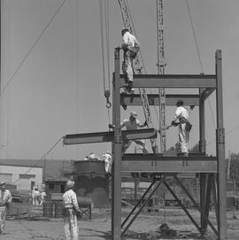 Structural steel, 1968; workers using a crane to place a side beam on a structure; people working...