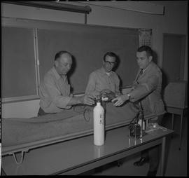 Industrial First Aid, Kelowna ; student and instructor adjusting levels on an oxygen tank, man ho...