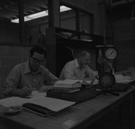 Stationary engineering upgrade, Victoria, 1968; two men sitting at a desk writing notes ; enginee...