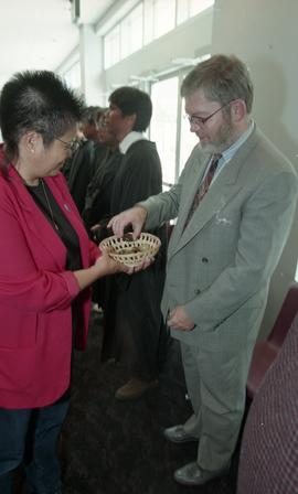 First Nations (?) woman presenting a wooden bowl filled with stones to staff member [3 of 3 photo...