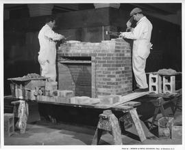 Bricklaying; two students building a brick fireplace in a workshop; Photo by the Division of Visu...
