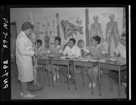 BCIT practical nursing students and staff in 1968 class and skeleton, medical posters behind