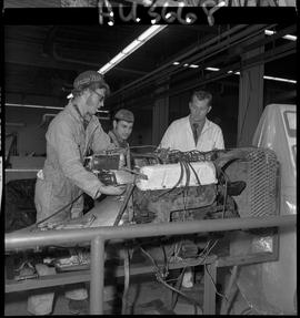 B.C. Vocational School image of an Instructor and Auto Mechanics program students working on auto...