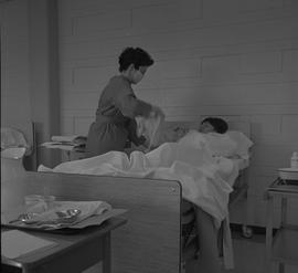Practical nursing, Prince George, 1968; nurse wearing a face mask attending to a patient [3 of 3]