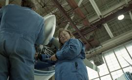 Canadian women at work; woman in uniform working on a jet engine with tools inside a hangar [2 of...