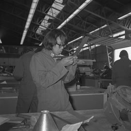 Sheet metal, 1968; student using a ruler to measure a thin strip of metal ; people working in bac...