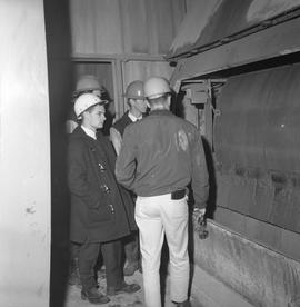 Forestry, Wood fiber BCIT tour, November 26, 1965; four men wearing hard hats standing next to a ...