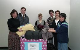 "Staff members with a box labeled ""Warm clothes and blankets for the needy"" [3 of 5 phot..."