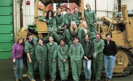 BCIT women in trades; heavy duty, students in uniforms standing in front of a bulldozer [8 of 9 p...