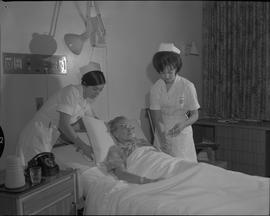 Nursing, 1967; two nurses attending to a patient checking temperature, pulse and respiration [1 o...
