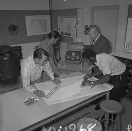 Navigation, 1968; two men measuring a nautical chart ; two men using navigational compasses [1 of 2]
