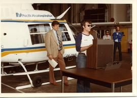 Aeronautical Accessories Inc. donates helicopter CA-ZX0 to PVI, men at podium in front of helicop...