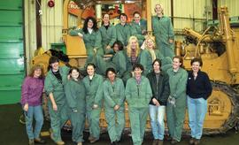 BCIT women in trades; heavy duty, students in uniforms standing in front of a bulldozer [6 of 9 p...