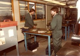Two men in workshop, coveralls