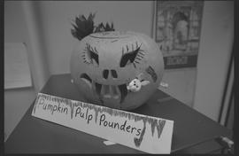 "Carved pumpkin with a ""pumpkin pulp pounders"" signs"