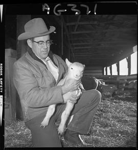B.C. Vocational School image of a lamb being held at Mile Zero Farm in Dawson Creek, BC.