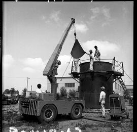 B.C. Vocational School image of Boilermaker students lowering part of the top on to a steel tank ...