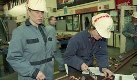 Trades discovery for women; piping/plumbing, students wearing hard hats and uniforms while using ...