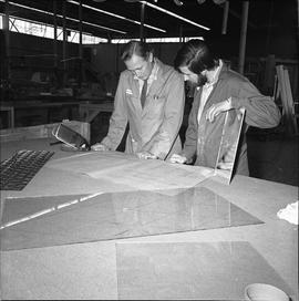 BCVS Glazier program ; two men looking at blueprints ; pieces of glass on the table