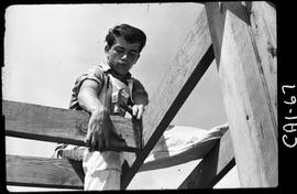 B.C. Vocational School image of a Carpentry Trades student outside sitting on rafters while naili...
