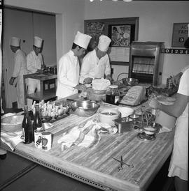 BC Vocational School Cook Training Course ; instructor supervising as student slices cheese ; stu...
