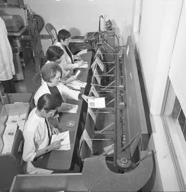 BCVS Graphic arts ; people adding folding papers to the conveyor for a staple binding machine [1 ...