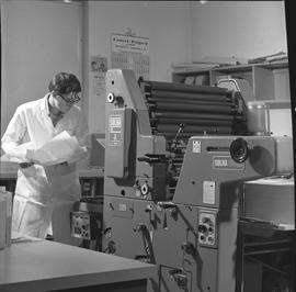 BCVS Graphic arts ; a man holding paper and looking at a printing press