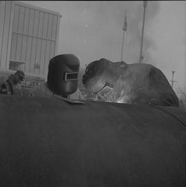 Welding, Nanaimo, 1968; two people wearing facemasks welding a large pipe