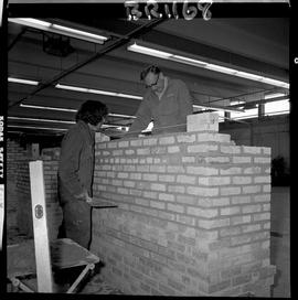 B.C. Vocational School image of a Bricklaying instructor teaching a student how to build a brick ...