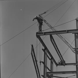 Structural steel, 1971; worker standing at the top of a steel structure; steel beam being moved u...