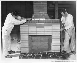Bricklaying; Two students measuring and hammering a brick fireplace; Photo by the Division of Voc...