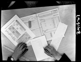 BCIT Business Management program documents sitting on a desk with a student making calculations.