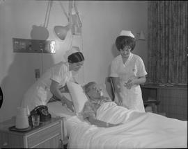 Nursing, 1967; two nurses attending to a patient checking temperature, pulse and respiration [2 o...