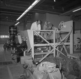 Marine engine repair, 1971; two students and an instructor looking at a boat motor in a wood fram...