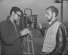 Survey, 1968; two men standing next to a theodolite on a tripod, one of the men writing notes