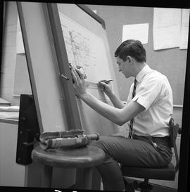BC Vocational School drafting course ; student sitting at an upright drafting desk and drawing