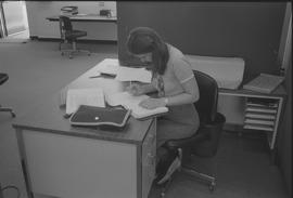 Pacific Vocational Institution ; student sitting at a desk and writing in a binder