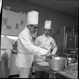 BC Vocational School Cook Training Course ; instructor (Arthur L. Brown) stirring a pot while a s...