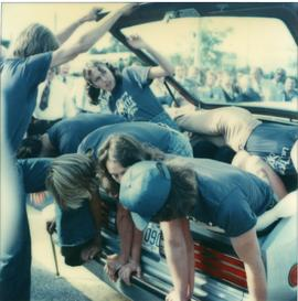 Student Rally 1984 ; students laying in or climbing into the trunk of a car