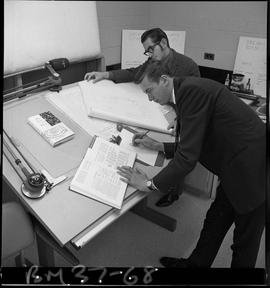 BCIT Business Management program image of two students working at a drafting table, using a chart...