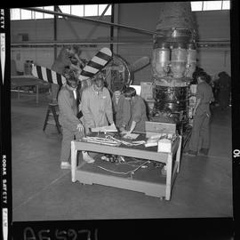 BC Vocational School; Aeronautics students and instructor gathered around a table, with aircraft ...