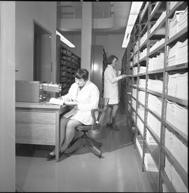 BCVS Graphic arts ; woman working at a desk ; woman organizing paper on a shelf [3 of 3]