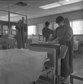 Practical nursing, Prince George, 1968; nurse wearing a face mask washing her hands ; nurse worki...