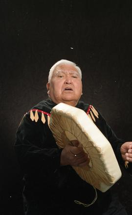 Bob George, First Nations elder, in First Nations garment playing an instrument [13 of 36 photogr...