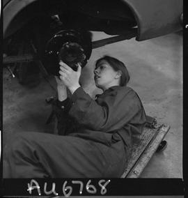 BC Vocational School image of a woman student in the Automotive Mechanics program working on the ...