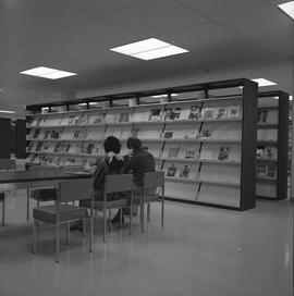 BCIT Burnaby campus library ; people sitting at a desk ; periodical shelves