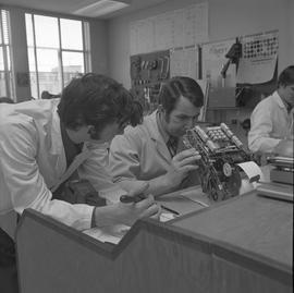 Office Machine Mechanic, 1968; man repairing a calculator and another man watching ; people worki...