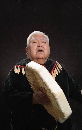 Bob George, First Nations elder, in First Nations garment playing an instrument [12 of 36 photogr...